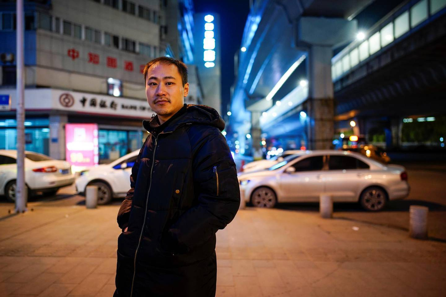 """An Junming poses for a picture on a street, almost a year after the global outbreak of the coronavirus disease (COVID-19) in Wuhan, Hubei province, China December 15, 2020. Junming who worked as a volunteer during the city's lockdown delivering food to people said: """"At that time, I could only eat one meal a day, because there was indeed a lot of work to do, but there were very few people doing it, so I was very anxious."""" Picture taken December 15, 2020. REUTERS/Aly Song"""
