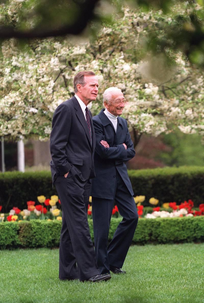 US President George Bush (L) gives French oceanographer Jacques-Yves Cousteau a tour of the White House Rose Garden, 24 April 1992. Le commandant Jacques-Yves Cousteau se promène dans les jardins de la Maison Blanche, le 24 avril 1992, avec le Président des Etats-Unis George Bush. (Photo by J. DAVID AKE / AFP)
