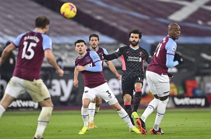 LONDON, ENGLAND - JANUARY 31: Mohamed Salah of Liverpool scores their side's first goal whilst under pressure from Aaron Cresswell of West Ham United during the Premier League match between West Ham United and Liverpool at London Stadium on January 31, 2021 in London, England. Sporting stadiums around the UK remain under strict restrictions due to the Coronavirus Pandemic as Government social distancing laws prohibit fans inside venues resulting in games being played behind closed doors. (Photo by Justin Setterfield/Getty Images)