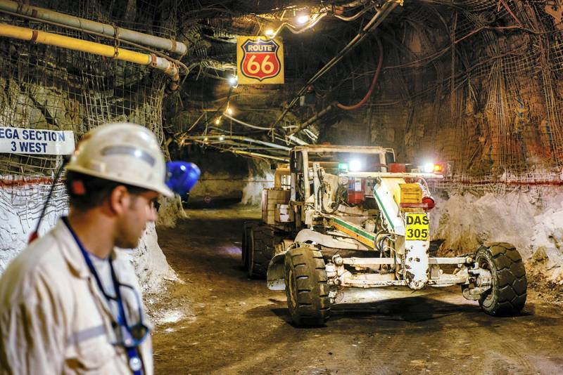 Heavy lifting equipment passes through an underground tunnel displaying a 'Route 66' highway sign at the South Deep gold mine, operated by Gold Fields Ltd., in Westonaria, South Africa, on Thursday, March 10, 2017. South Deep is the world's largest gold deposit after Grasberg in Indonesia, makes up 60 percent of the company's reserves and the miner says it's capable of producing for 70 years. Photographer: Waldo Swiegers/Bloomberg