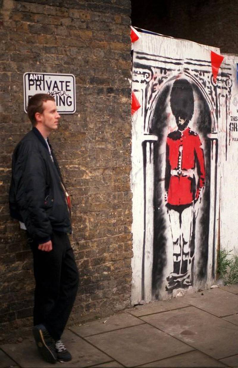 LON01 - 20020531 - LONDON, UNITED KINGDOM : People take a look at a painting by Banksy, one of London's foremost street artists, to celebrate the Queen's Jubilee 30 May 2002, in Clink street, near London Bridge. Banksy, a  graffiti artist uses the streets as his gallery to put across his views in an original way.  EPA PHOTO EPA / BEN FATHERS