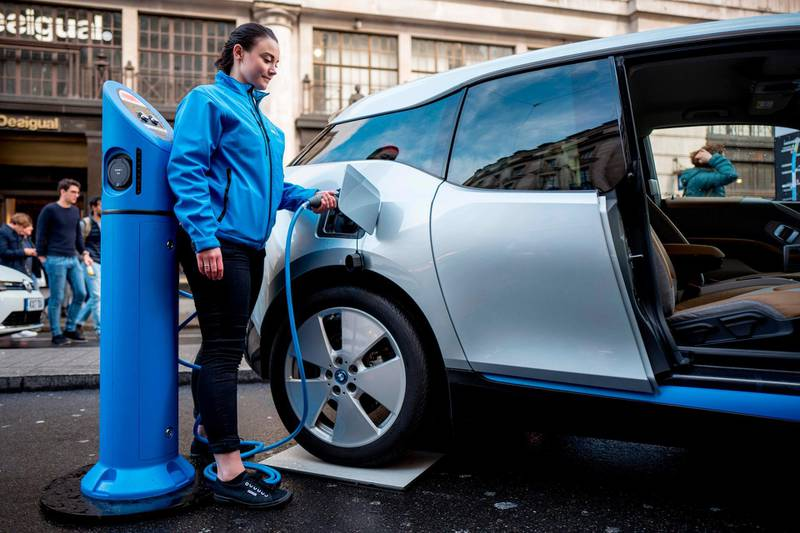 """A BMW staff member poses for a photograph as she connects a BMW i3 electric vehicle (EV) to a charging point during Regent Street Motor Show on November 4, 2017 in London.  A driverless, electric car is only a swipe away in the cities of the future, where pollution clampdowns and rapid advances in technology will transform the way we travel, despite lagging infrastructure. A switch from petrol to electric vehicles (EVs) is under way. Britain and France intend to ban the sale of fully petrol or diesel cars from 2040, while smog-plagued India wants to sell only electric cars by 2030.  Expert motoring journalist Matt Robinson said a """"woeful lack"""" of suitable charging points remained a big problem for electric car users. / AFP PHOTO / TOLGA AKMEN"""
