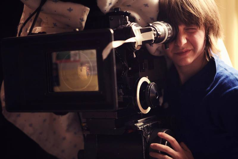 """""""A young woman operating a 35mm film camera. There is a blanket thrown over the camera to dampen the sound of the film running through it so it doesn't interfere with the scene.Shot on a real set at high iso, some noise, view at 100%.More filmmaking images:"""" Getty Images"""