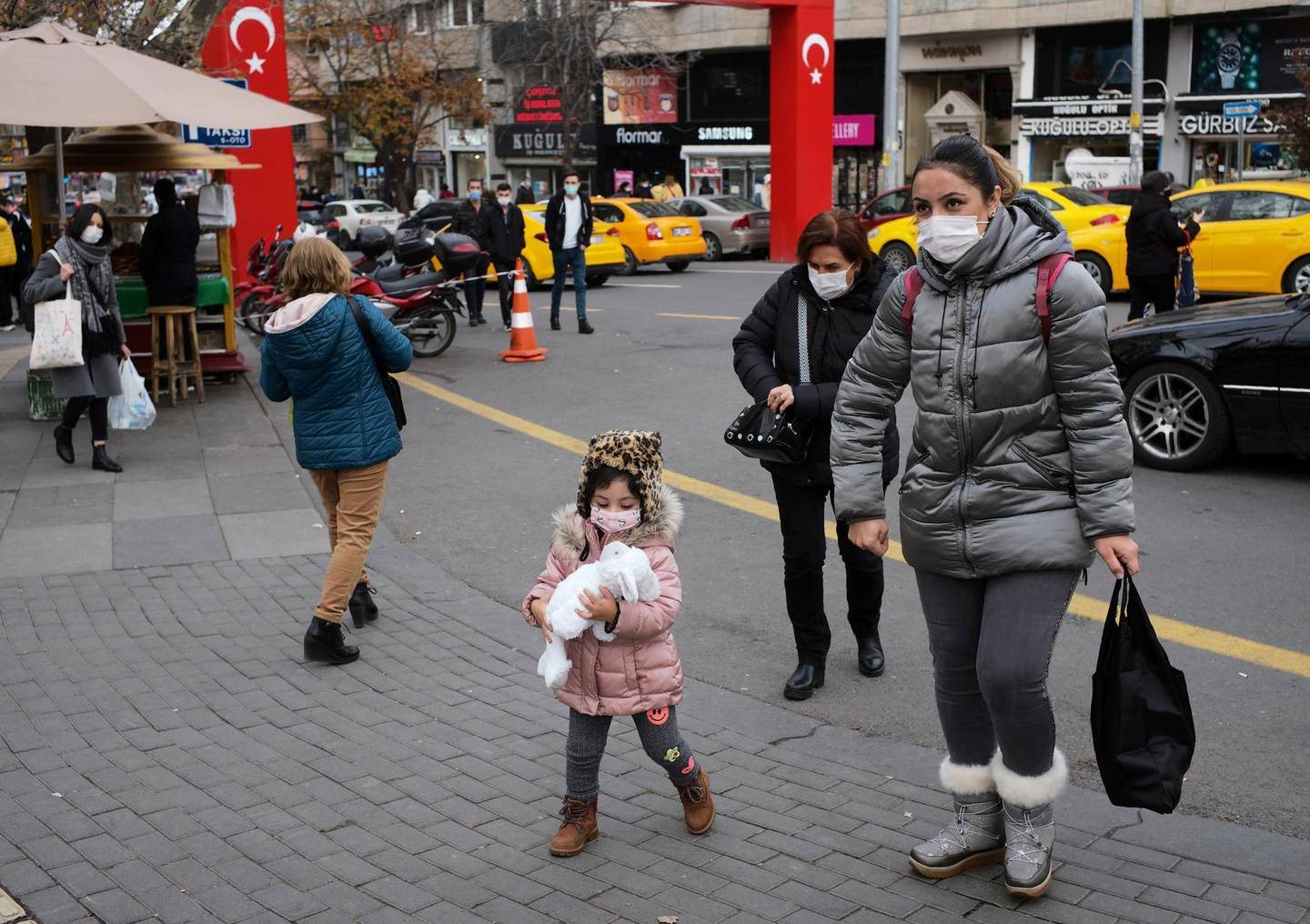 People wearing face masks to protect against coronavirus, walk along a street hours before a two-day weekend curfew, in Ankara, Turkey, Friday, Dec. 18, 2020. Turkey's daily COVID-19 death toll hit a record high on Wednesday, Dec. 16, 2020, with the government announcing close to 30,000 new confirmed infections in the last 24 hours, pushing the total of confirmed cases since the outbreak began in March to nearly 2 million. (AP Photo/Burhan Ozbilici)