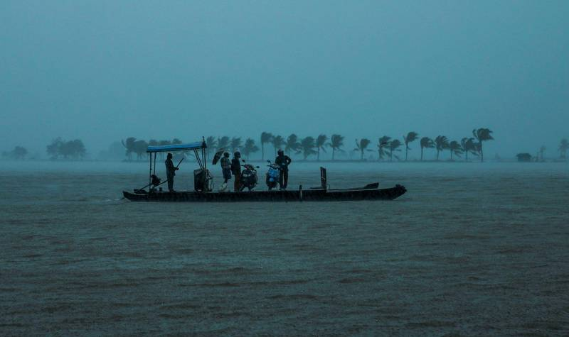 TOPSHOT - Residents are being evacuated from their home to a safer place following floods warnings, on a wooden boat at Kadamakkudi near Kochi in the Indian state of Kerala on August 10, 2019.  Floods have killed at least 100 people and displaced hundreds of thousands across much of India with the southern state of Kerala worst hit, authorities said on August 10. / AFP / STR