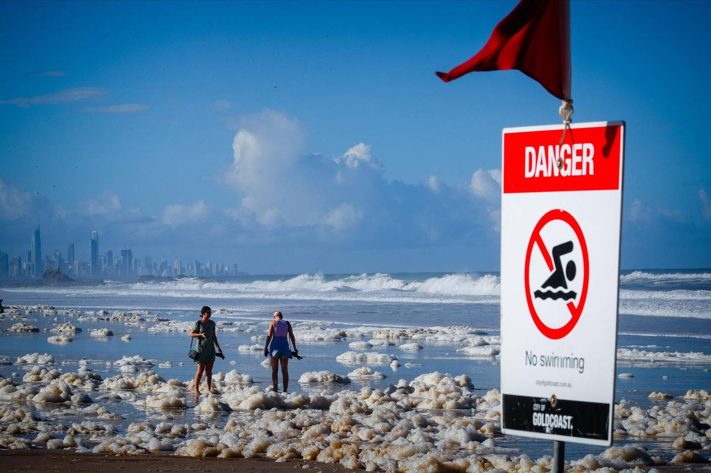 Tourists walk amongst beach foam in the wake of cyclonic conditions at Currumbin Beach on December 15, 2020, after wild weather lashed Australia's Northern New South Wales and South East Queensland with heavy rain, strong winds and king tides. / AFP / AFP  / Patrick HAMILTON