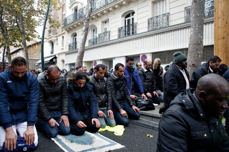 Muslims pray in the street for Friday prayer in the Paris suburb of Clichy la Garenne, Friday, Nov. 10, 2017. Tensions have erupted as residents and the mayor of a Paris suburb tried to block the town's Muslims from praying in the street in a dispute that reflects nationwide problems over mosque shortages. (AP Photo/Thibault Camus)