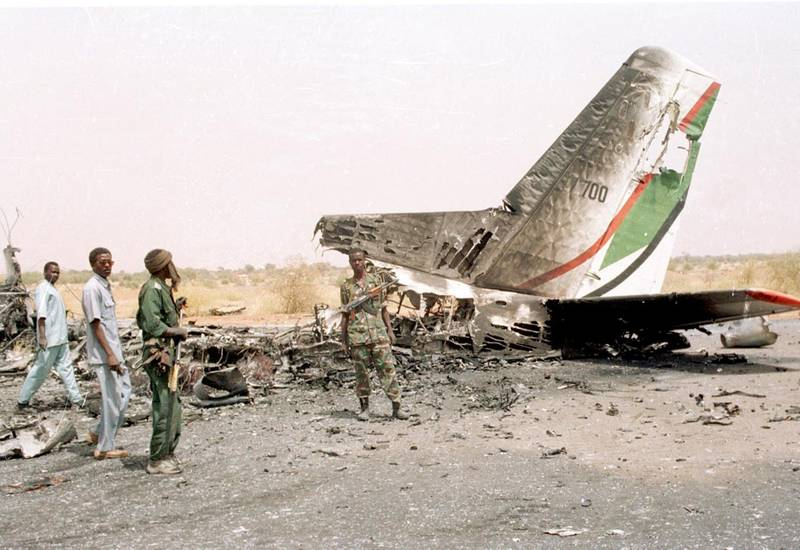 """Sudanese soldiers look at a plane destroyed by the rebels on the North Darfur state capital of Al-Fasher 29 April 2003. Thousands of villagers have reportedly fled their villages since April 11 after fighting between government forces and the Sudan Liberation Army (SLA). Khartoum has refused to acknowledge any political motivation for unrest in the Darfur states, blaming it instead on """"armed criminal gangs and outlaws,"""" who it says are aided by tribes from neighboring Chad. AFP PHOTO/Salah OMAR (Photo by SALAH OMAR / AFP)"""