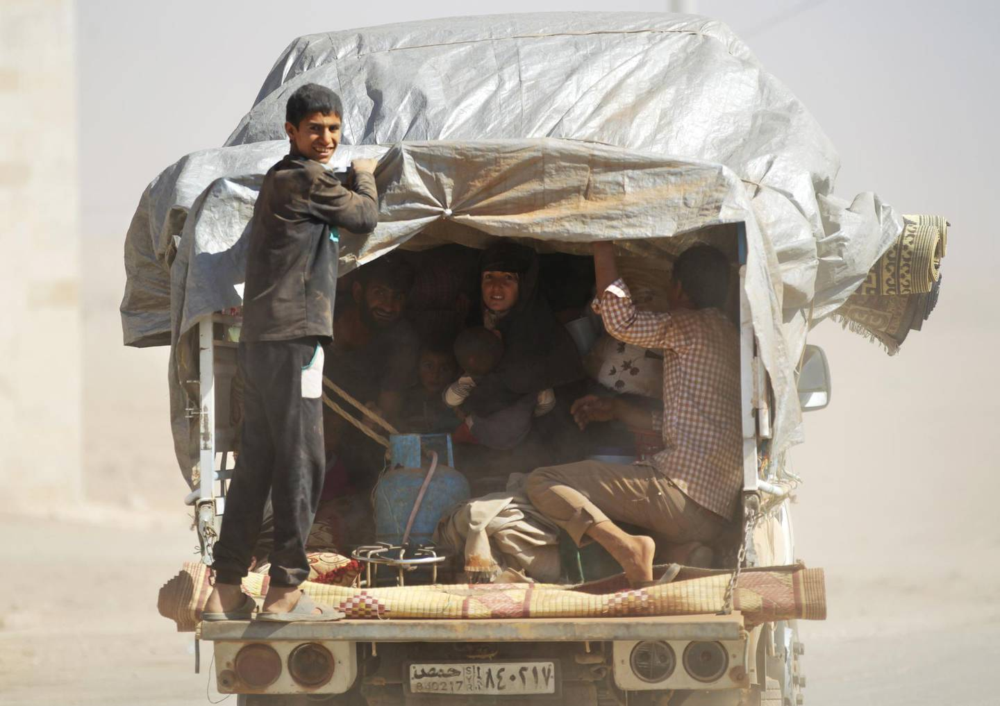 People, who fled from Islamic State-controlled areas, ride a pick-up truck upon their arrival in Turkman Bareh village, after rebel fighters advanced in the area, in northern Aleppo Governorate, Syria, October 7, 2016. REUTERS/Khalil Ashawi