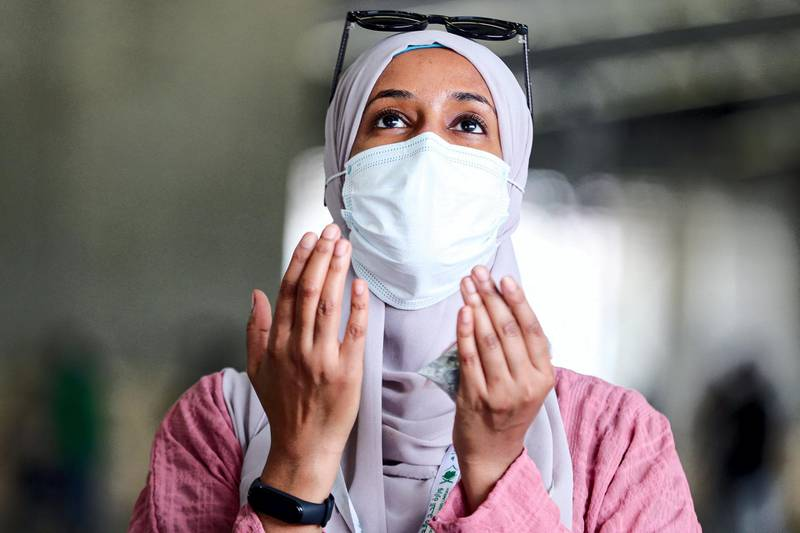 A woman Muslim pilgrim, clad in a face mask due to the COVID-19 coronavirus pandemic, prays after throwing pebbles as part of the symbolic al-A'qabah (stoning of the devil ritual) at the Jamarat Bridge during the Hajj pilgrimage in Mina, near Saudi Arabia's holy city of Mecca, on August 2, 2020. - Massive crowds in previous years triggered deadly stampedes during the ritual, but this year only up to 10,000 Muslims are taking part after millions of international pilgrims were barred because of the covid-19 pandemic crisis. (Photo by - / AFP)