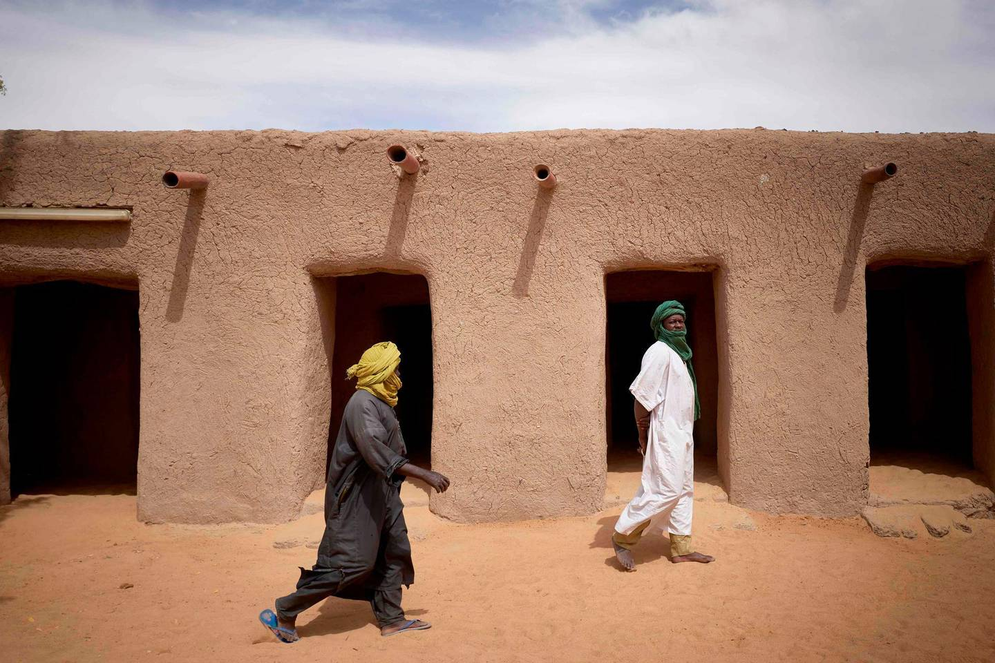 Malian faithfuls walk in the courtyard of the Tomb of Askia in Gao on March 10, 2020. The site, which was protected during the 10 months of jihadist occupation in 2012, represents one of the finest examples of Sudano-Sahelian architecture in the Sahel region. / AFP / MICHELE CATTANI