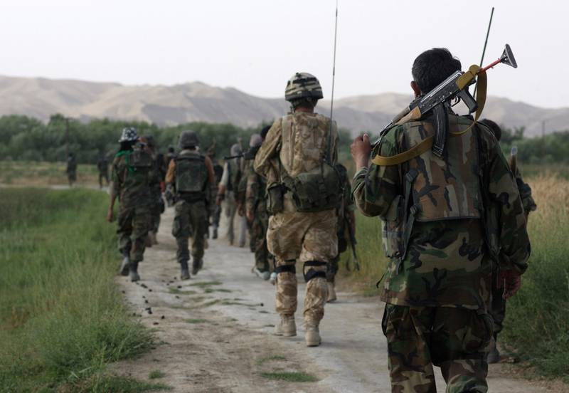 """HELMAND PROVINCE, AFGHANISTAN - JUNE 1: British Army Officer, Captain Alex Corbet Burcher from the 1st Battalion Welsh Guards Regiment,attached to the Inkerman Company, 1st Battalion Grenadier Guards Regiment patrols with ANA (Afghan National Army) Soldiers his area of operation  during """"Lastay Kulang"""" Operation"""" on June 1, 2007 in Sangin Valley, Helmand Province, Afghanistan. British troops from The Inkerman Company, 1st Battalion Grenadier Guards, part of ISAF Task Force Helmand, are mentoring the Afghan National Army while conducting security operations on behalf of the Government of Afghanistan in Helmand Province.(Photo by Marco Di Lauro/Getty Images)"""