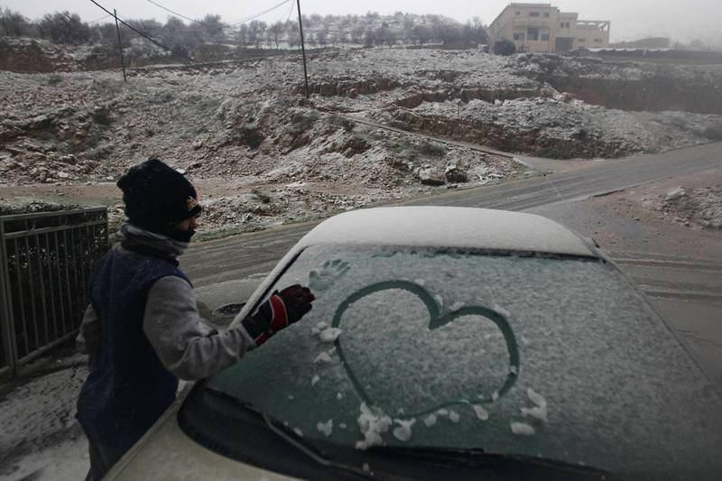 A boy makes a print of his hand on a car windscreen covered with snow before clearing it, during stormy weather in the Druze village of Majdal Shams on the Golan Heights January 8, 2013. REUTERS/Ammar Awad (ENVIRONMENT) *** Local Caption ***  JER27_ISRAEL-STORM-_0108_11.JPG
