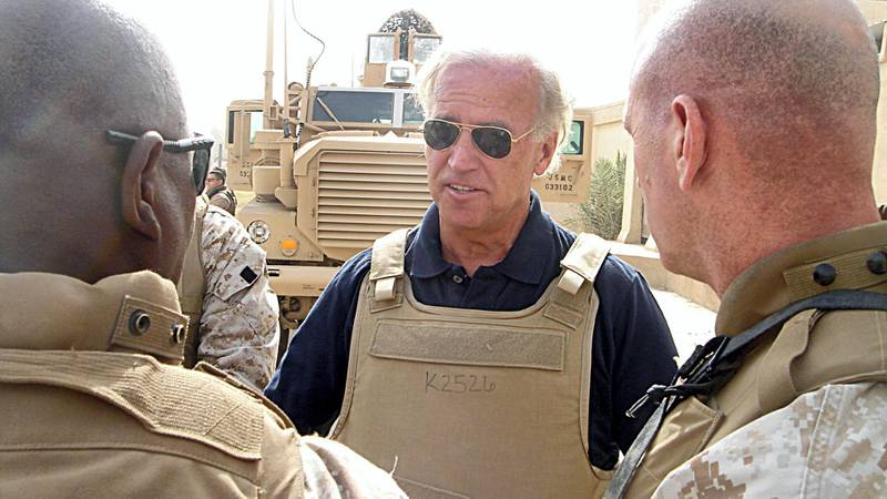 This 06 September, 2007 photo, courtesy of US Senator Joseph Biden's office, shows the Demoratic Delaware Senator(C) speaking with unidentified soldiers about the effectiveness and life-saving technology of the Mine Resistant Ambush Protected (MRAP) vehicle(rear) during a visit to Ramadi, Iraq. AFP PHOTO/HO/Courtesy of Senator Biden's office/RESTRICTED TO EDITORIAL USE/ GETTY OUT (Photo by HO / Joe Biden / AFP)