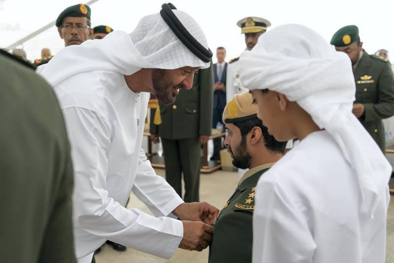 ABU DHABI, UNITED ARAB EMIRATES - April 23, 2018: HH Sheikh Mohamed bin Zayed Al Nahyan Crown Prince of Abu Dhabi Deputy Supreme Commander of the UAE Armed Forces (L), awards HH Sheikh Zayed bin Hamdan bin Zayed Al Nahyan (2nd R), with a Medal of Bravery for his service in Yemen, during a Sea Palace barza. Seen with HH Sheikh Rashid bin Hamdan bin Zayed Al Nahyan (R).  ( Rashed Al Mansoori / Crown Prince Court - Abu Dhabi )