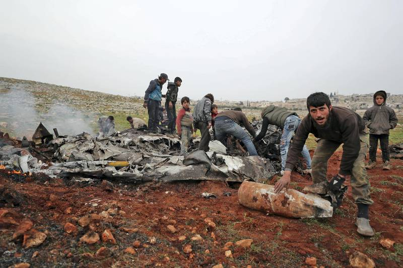 People search for scraps of metal among the debris of a Syrian military helicopter that was shot down on February 14, 2020, in the western countryside of Aleppo province. - The  helicopter was shot down over the last major rebel bastion in northwest Syria, killing two pilots, a war monitor said, in the second such incident this week. (Photo by Omar HAJ KADOUR / AFP)