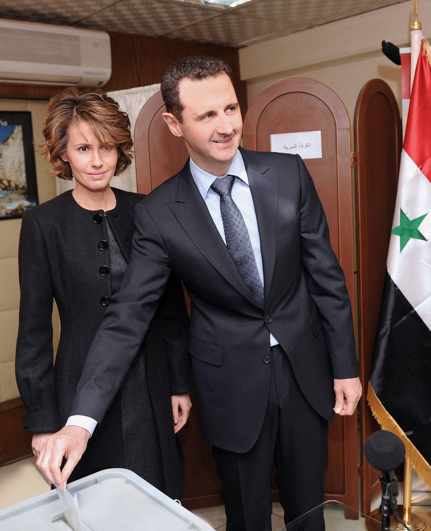 """(FILES) This file handout picture released by the Syrian Arab News Agency (SANA) shows Syrian President Bashar al-Assad (R) and his wife Asma (L) voting on the constitution that could end five decades of single-party domination in Damascus. A decade of war may have ravaged his country, but Syria's President Bashar al-Assad has clung to power and looks determined to cement his position in presidential elections this year. / AFP / SANA / - / RESTRICTED TO EDITORIAL USE - MANDATORY CREDIT """"AFP PHOTO / HO / SANA"""" - NO MARKETING NO ADVERTISING CAMPAIGNS - DISTRIBUTED AS A SERVICE TO CLIENTS"""