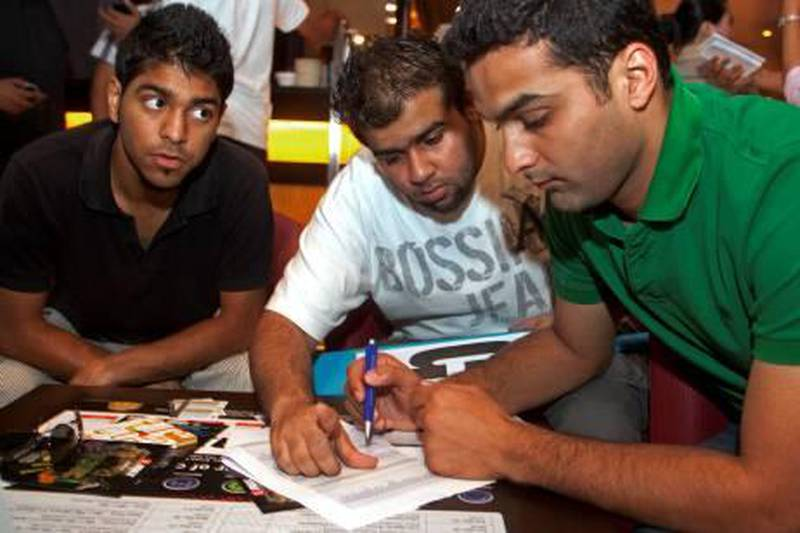 Dubai, March 21, 2011 - Members of team Chill Meena from left Zoheb Mustafa watches as Sagar Ankolekar helps Prithvi Adnani select cricket players their team, one of 16 participating in the auction, will bid on during a cricket World Cup fantasy auction in the Sports Lounge of the Citymax Hotel in Bur Dubai, Dubai March 21, 2011. (Jeff Topping/The National)