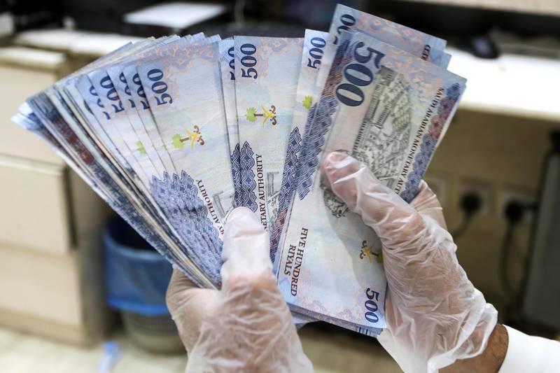 A Saudi money exchanger wears gloves as he counts Saudi riyal currency at a currency exchange shop in Riyadh, Saudi Arabia March 10, 2020. REUTERS/Ahmed Yosri