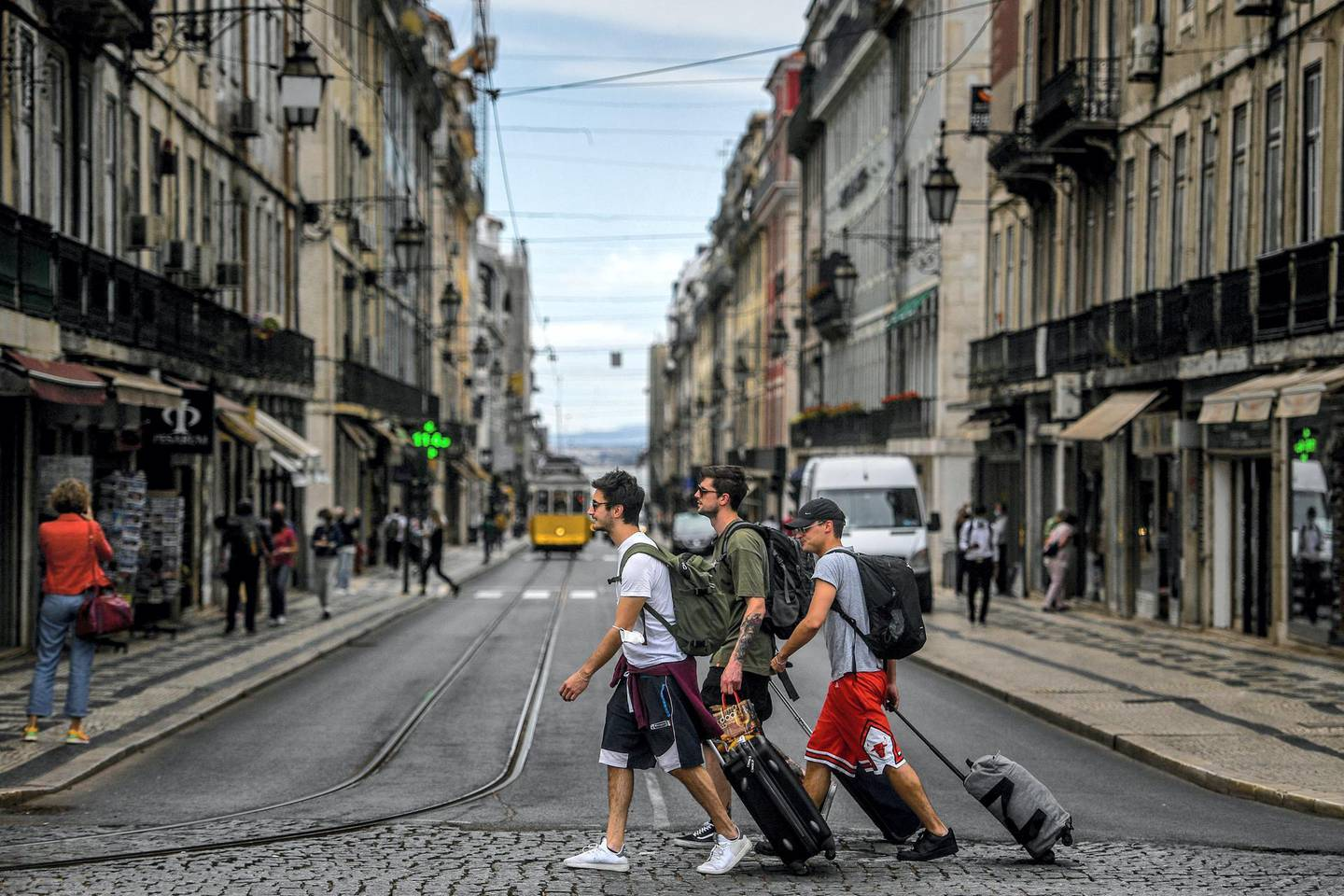 Tourist cross a street in downtown Lisbon on June 18, 2021. - The Portuguese government will limit travel to and from the greater Lisbon area during the weekend following an increase in coronavirus cases in the region. (Photo by PATRICIA DE MELO MOREIRA / AFP)