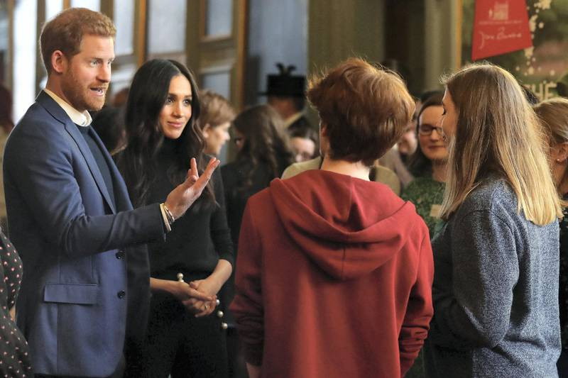 Britain's Prince Harry (L) and his fiancée US actress Meghan Markle (2nd L) attend a reception for young people in the Palace of Holyroodhouse in Edinburgh, during their visit to Scotland on February 13, 2018. - The reception celebrates youth achievements, marking Scotland's Year of Young People 2018, an initiative that aims to inspire Scotland through its young people: celebrating their achievements, strengthening their voice on social issues and creating new opportunities for them to shine. (Photo by Andrew Milligan / POOL / AFP)