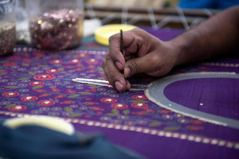 In this photo taken on February 14, 2020, a man works on an embroidery at the factory of fashion deisgner Anita Dongre on the outskirts of Mumbai. With stores in India and New York, multiple clothing brands and a global celebrity following, fashion designer Anita Dongre is a feminist powerhouse in a male-dominated industry. But her true ambition is to create an environmentally sustainable company, she says. - TO GO WITH Women-activism-India-fashion-economy-environment,INTERVIEW by Ammu Kannampilly  / AFP / Laurène Becquart / TO GO WITH Women-activism-India-fashion-economy-environment,INTERVIEW by Ammu Kannampilly
