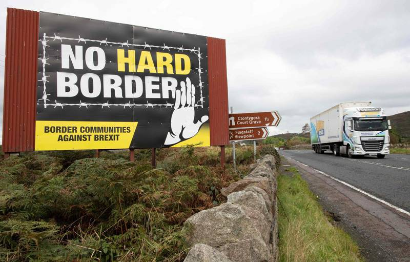 """A vechile passes an anti-Brexit pro-Irish unity billboard seen from the Dublin road in Newry, Northern Ireland, on October 1, 2019 on the border between Newry in Northern Ireland and Dundalk in the Irish Republic.  Britain will give the EU new proposals for a Brexit deal """"shortly"""", Prime Minister Boris Johnson said on October 1, but rejected reports it would see customs posts along the Irish border.   / AFP / PAUL FAITH"""