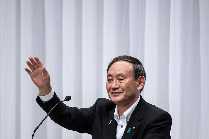 FILE PHOTO: Japan's Chief Cabinet Secretary Yoshihide Suga waves after a debate organized by the Liberal Democratic Party, Youth Bureau and Women's Bureau at the LDP headquarters in Tokyo, Japan September 9, 2020. Philip Fong/Pool via REUTERS/File Photo
