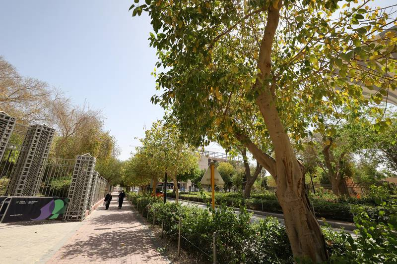 """People walk on a tree-lined sidewalk in the Saudi capital Riyadh, on March 29, 2021. - Although the OPEC kingpin seems an unlikely champion of clean energy, the """"Saudi Green Initiative"""" aims to reduce emissions by generating half of its energy from renewables by 2030. (Photo by Fayez Nureldine / AFP)"""