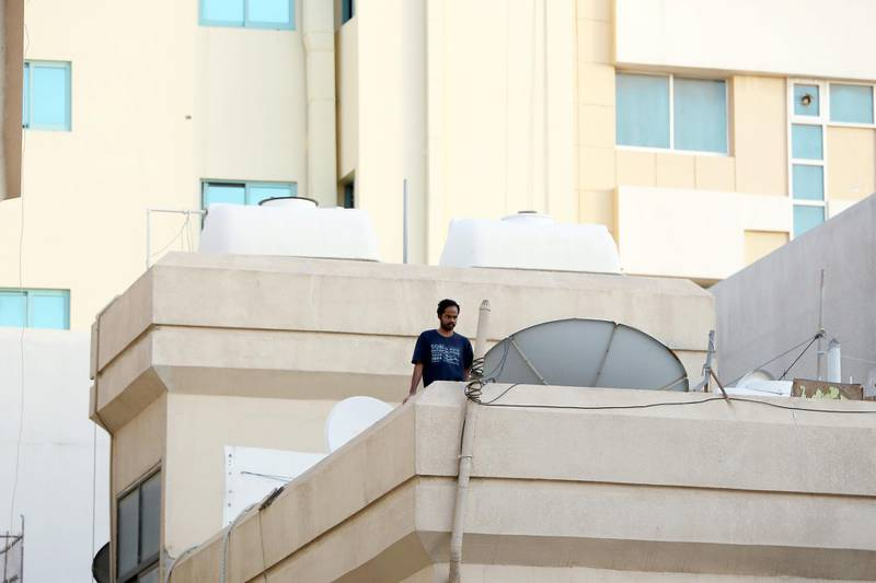 DUBAI, UNITED ARAB EMIRATES , April 27 – 2020 :- A resident looking at the streets from his home in Al Ras area in Deira Dubai. Authorities ease the restriction for the residents after almost a month long locked down of Al Ras district. (Pawan Singh / The National) For News/Standalone/Online/Instagram