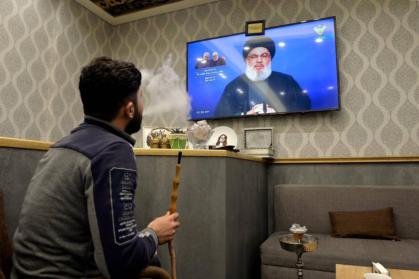 epa08122250 A Lebanese man smokes water pipe as he watches the speech of Hezbollah leader Hassan Nasrallah on a television screen at a cafe to mark the one-week death of slain the Iranian Revolutionary Guards Corps (IRGC) Lieutenant general and commander of the Quds Force Qasem Soleimani in Beirut, Lebanon, 12 January 2020. The US Pentagon announced that Iran's Quds Force leader Soleimani and Iraqi militia commander Abu Mahdi al-Muhandis were killed on 03 January 2020 following a US airstrike at Baghdad's international airport.  EPA/WAEL HAMZEH