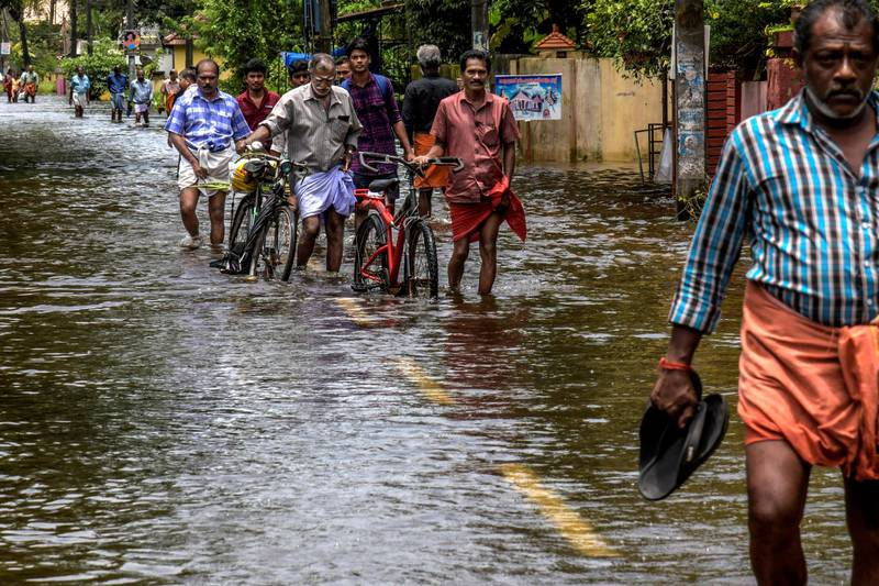 KERALA, INDIA - AUGUST 20: Locals cross flood water on route to  Chengannur on August 20, 2018 in Kerala, India. Over 350 people have reportedly died in the southern Indian state of Kerala after weeks of monsoon rains which caused the worst flooding in nearly a century. Officials said more than 800,000 people have been displaced and taken shelter in around 4,000 relief camps across Kerala as the Indian armed forces step up efforts to rescue thousands of stranded people and get relief supplies to isolated areas. (Atul Loke/Getty Images)