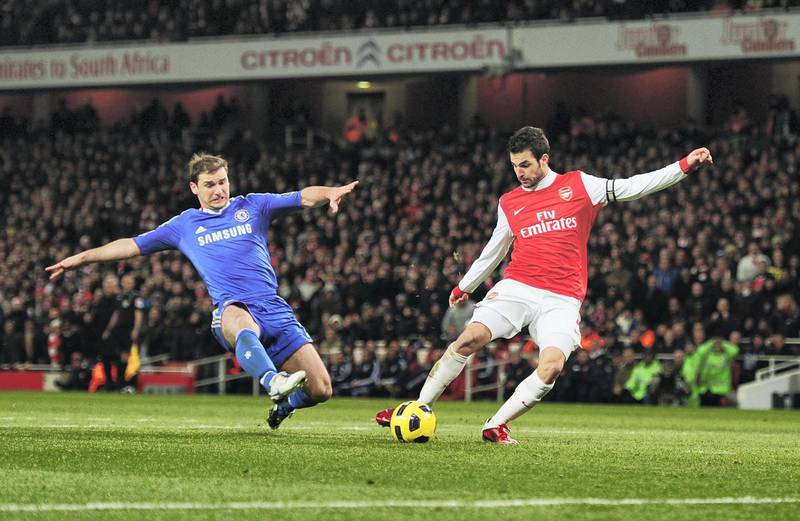 LONDON, ENGLAND - DECEMBER 27: Cesc Fabregas of Arsenal shoots to score Arsenal's second goal despite a challenge by Branislav Ivanovic of Chelsea during the Barclays Premier League match between Arsenal and Chelsea at the Emirates Stadium on December 27, 2010 in London, England.  (Photo by Shaun Botterill/Getty Images)