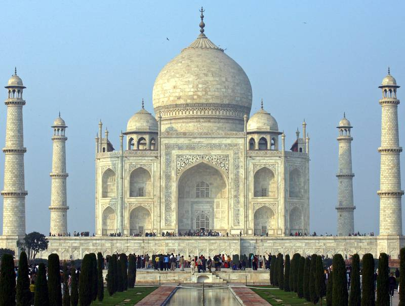 Tourists stand in front of the historic Taj Mahal in the northern Indian city of Agra January 17, 2009. The Taj Mahal was built by Emperor Shah Jahan in memory of his wife and is one of the world's most famous monuments. REUTERS/Vijay Mathur (INDIA) - GM1E51I0E5W01