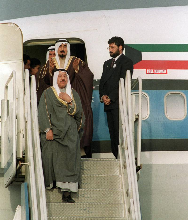 """Sheikh Jaber al-Ahmad al-Sabah (top), Emir of Kuwait, prays as he disembark his plane 14 March 1991 upon his arrival at Kuwait International Airport after more than seven months in exile during the Iraqi occupation of his country. A US-led multinational coalition evicted Iraqi occupation forces in February 1991 at the end of the six-week conflict. Three years later, Iraq officially recognized the state of Kuwait and its UN-demarcated borders. MP Uday Saddam Hussein, the elder son of the Iraqi president, has renewed 15 January 2001 claims to Kuwait as forming part of a """"Greater Iraq"""", in an except of a report to parliament in Baghdad. (Photo by BOB PEARSON / AFP)"""