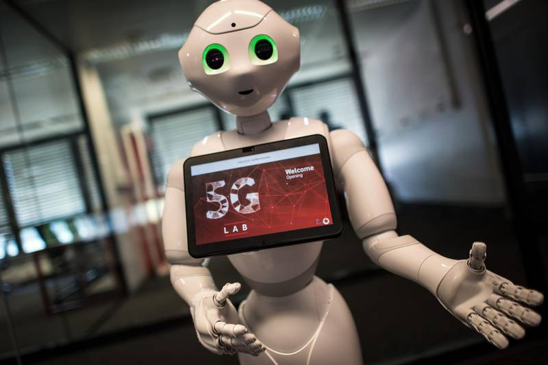 """Robot """"Pepper"""" welcomes guests arriving for the opening of the Vodafone 5G Lab in Duesseldorf, western Germany, on May 9, 2018. At the lab, all devices able to be run under the 5th generation wireless systems (5G wireless network technology) will be tested for the network of mobile telecommunications operator Vodafone. / AFP PHOTO / dpa / Federico Gambarini / Germany OUT"""