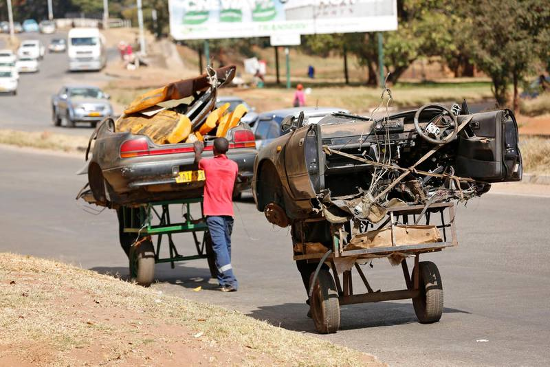 epa07608445 Men pull and push carts laden with half pieces of a what was once a motor vehicle in Harare, Zimbabwe, 28 May 2019.The vehicle will be stripped apart and the scrap metal to be sold to earn a living. Zimbabweans are facing economic challenges as prices of almost everything rising everyday.  EPA/AARON UFUMELI