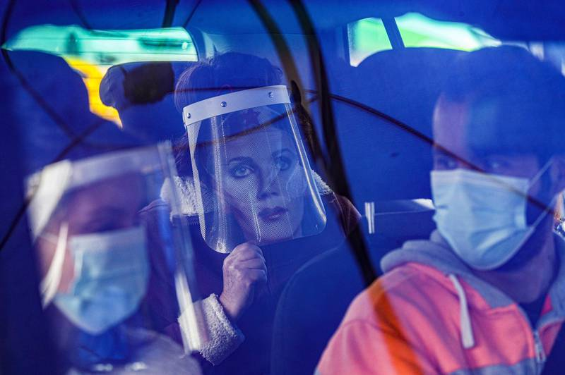 Marisol Aro, wearing a face shield with an image of Wonder Woman, looks out from a car, amid the new coronavirus pandemic in Santiago, Chile, Saturday, June 27, 2020. Aro's husband bought her the face shield who has since been infected with the new coronavirus and is now intubated in an intensive care unit. (AP Photo/Esteban Felix)