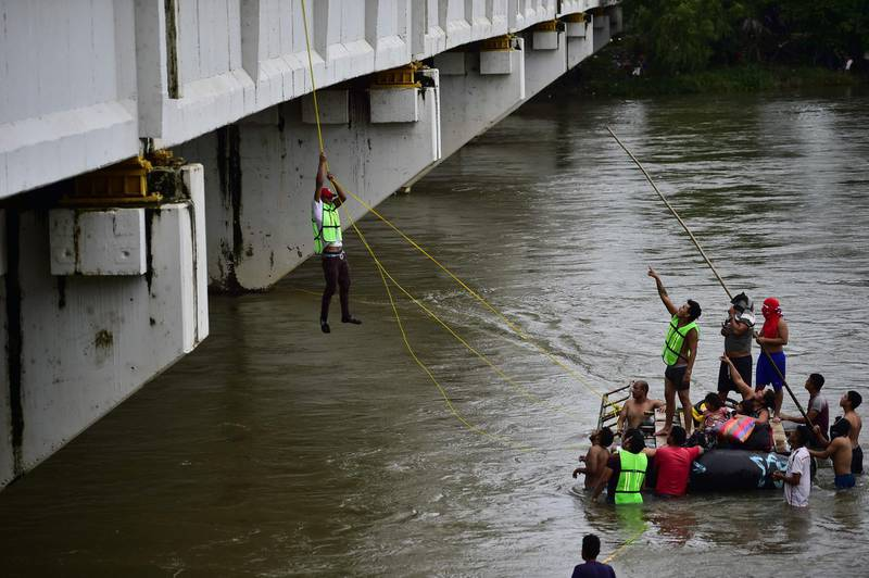 Honduran migrants heading in a caravan to the US, help a fellow man get down to the Suchiate River from the Guatemala-Mexico international border bridge, in Ciudad Hidalgo, Chiapas state, Mexico, on October 20, 2018.  Thousands of migrants who forced their way through Guatemala's northwestern border and flooded onto a bridge leading to Mexico, where riot police battled them back, on Saturday waited at the border in the hope of continuing their journey to the United States. / AFP / Pedro Pardo