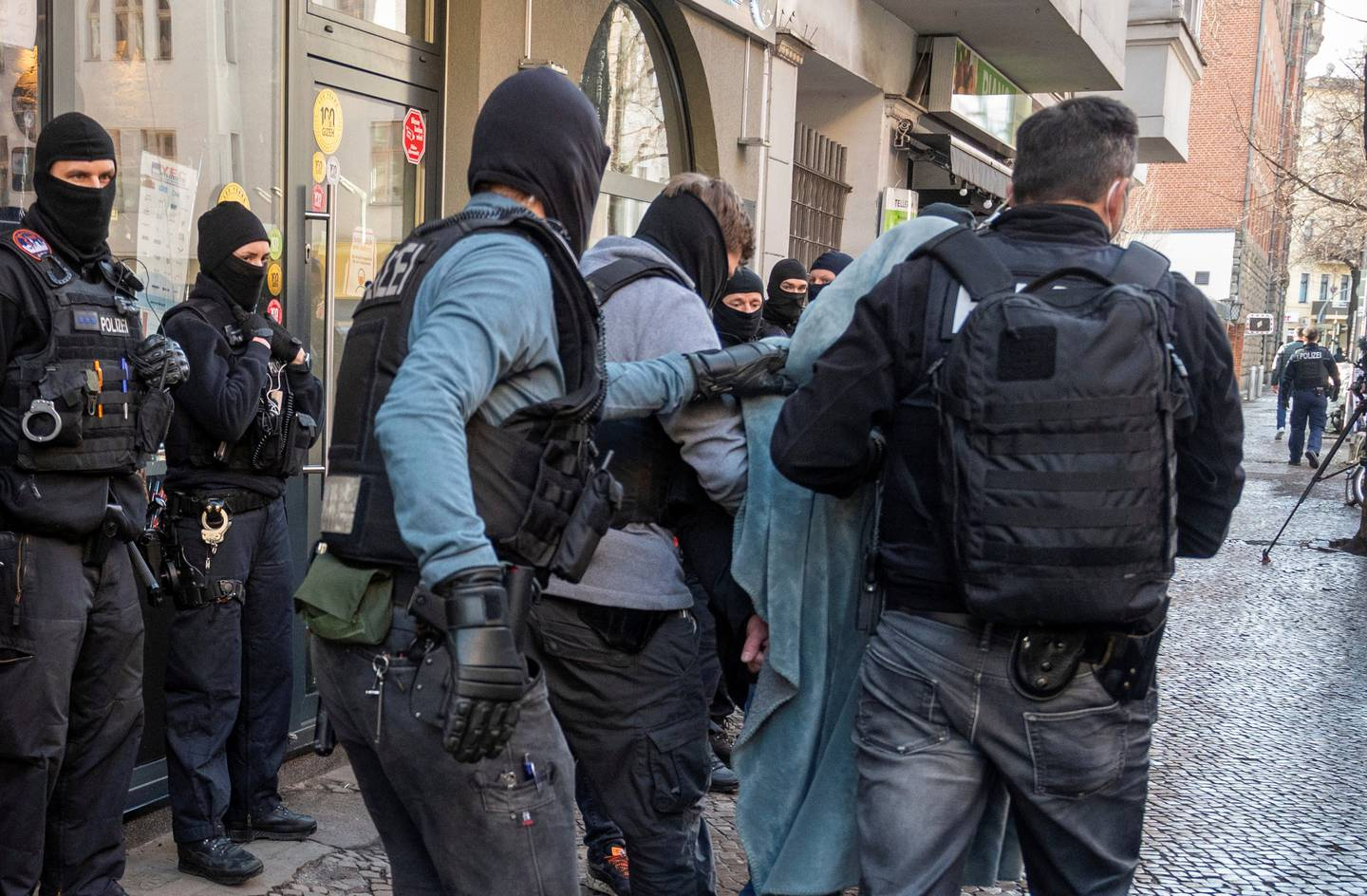 A man is led away by police with a blanket over his head during a raid in Berlin, Germany, on Thursday, February 18, 2021. The police attacked clan crimes in Berlin and the surrounding area with a major raid on Thursday morning.  (Christophe Gateau / dpa via AP)