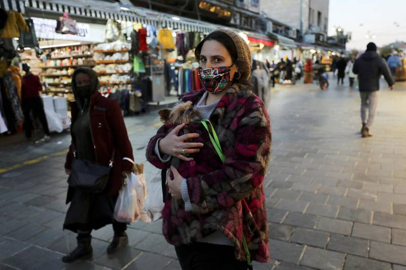 A woman holds a dog as she walks before Israel imposes a third national lockdown to fight climbing coronavirus disease (COVID-19) infections, in Jerusalem December 27, 2020. REUTERS/Ammar Awad