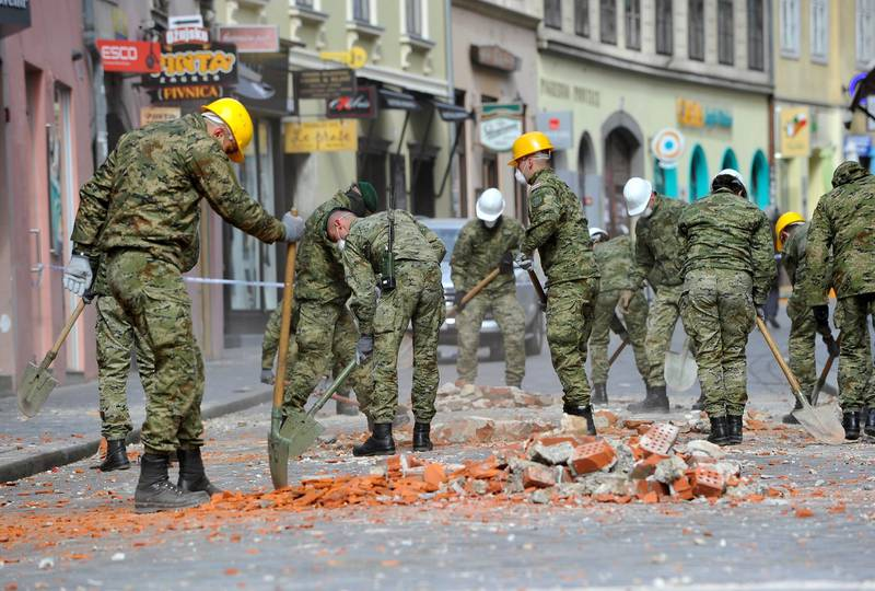 Croatian soldiers clear debris from the street after an earthquake in Zagreb, Croatia, Sunday, March 22, 2020. A strong earthquake shook Croatia and its capital on Sunday, causing widespread damage and panic. (AP Photo)