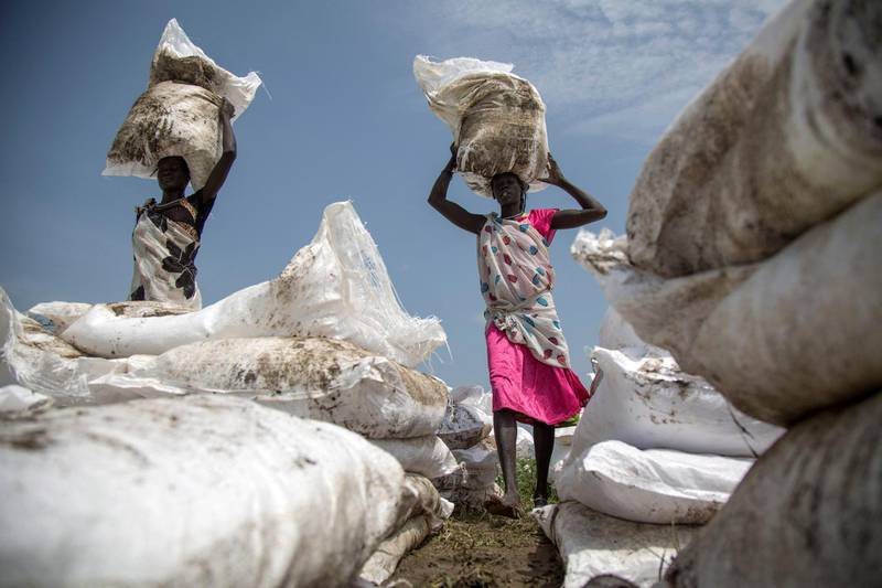 Women carry sacks of food, airdropped by the World Food Programme and distributed by the NGO Oxfam in Padding, near Lankien, Jonglei, South Sudan, on July 3, 2017. - Fighting between Government and opposition forces in April 2017 pushed thousands of civilians to be displaced in Padding and Lankien, both are still under opposition control. The massive displacement brought an outbreak of cholera and a serious need of health assistance, drinking water and food distribution among the population, according to the local leaders. (Photo by ALBERT GONZALEZ FARRAN / AFP)