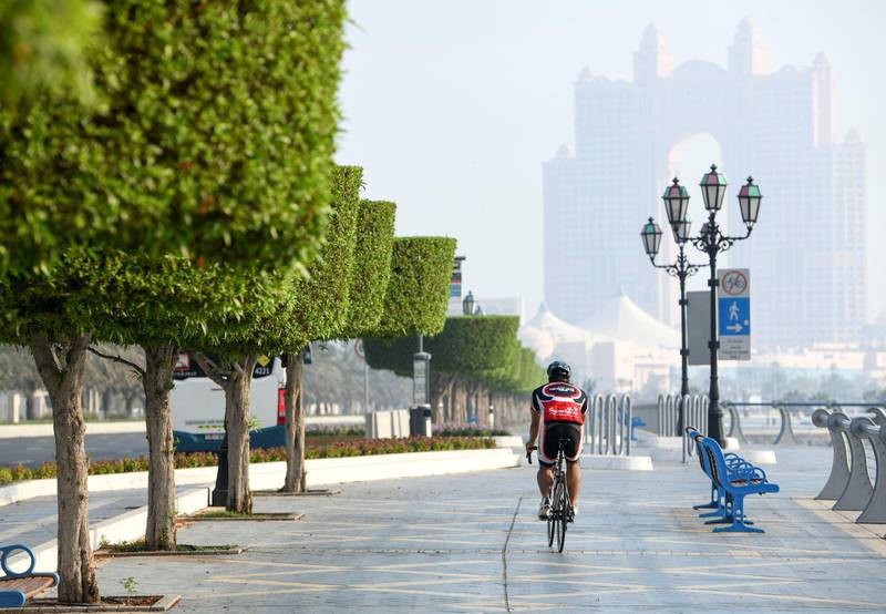 Morning-AD  Residents cycle during low visibility along the Corniche, in Abu Dhabi on June 5, 2021. Khushnum Bhandari / The National  Reporter: N/A News