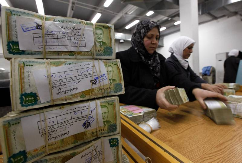 FILE - In this January 13, 2010 file photo, Syrian employees stack packets of Syrian currency in the Central Syrian Bank in, Damascus, Syria. In Syria nowadays, there is an impending fear that all doors are closing. After nearly a decade of war, the country is crumbling under the weight of years-long western sanctions, government corruption and infighting, a pandemic and an economic downslide made worse by the financial crisis in Lebanon, Syria's main link with the outside world. (AP Photo/Hussein Malla, File)
