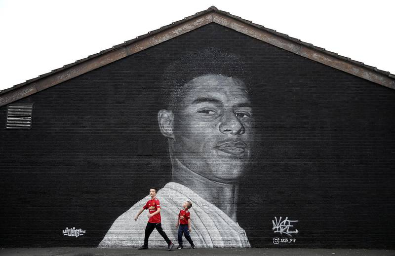 Jacob (left) and Joshua Hallighan in-front of a mural of Manchester United striker Marcus Rashford by Street artist Akse on the wall of the Coffee House Cafe on Copson Street, Withington. PA Photo. Picture date: Sunday November 8, 2020. Manchester United forward Marcus Rashford has drawn widespread praise for his role in highlighting the issue of child food poverty, which has been exacerbated by the economic impact of the coronavirus pandemic. See PA story SOCCER Rashford. Photo credit should read: Martin Rickett/PA Wire. (Photo by Martin Rickett/PA Images via Getty Images)