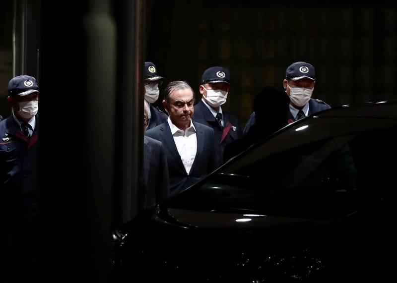 """(FILES) In this file photo taken on April 25, 2019 former Nissan chairman Carlos Ghosn (C) is escorted as he walks out of the Tokyo Detention House following his release on bail in Tokyo.   A year after Japan learned with horror that Carlos Ghosn had jumped bail to become the world's most famous fugitive, the fiasco and its repercussions continue to haunt the country. Ghosn was living in a monitored Tokyo apartment awaiting trial on financial misconduct charges when he casually boarded a train to Osaka in western Japan on December 29, 2019 with two accomplices. - TO GO WITH AFP FOCUS """"JAPAN-GHOSN-AUTOMOBILE-LEBANON-NISSAN-RENAULT"""" BY ETIENNE BALMER   / AFP / Behrouz MEHRI / TO GO WITH AFP FOCUS """"JAPAN-GHOSN-AUTOMOBILE-LEBANON-NISSAN-RENAULT"""" BY ETIENNE BALMER"""
