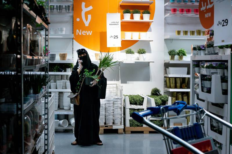 A customer carries plant purchases and uses her mobile phone while shopping in an Ikea AB store in Riyadh, Saudi Arabia, on Tuesday, May 19. 2020. Before the pandemic, most shops, pharmacies and gas stations in the kingdom halted for at least 30 minutes for each prayer session, the only country that enforced such closures. Photographer: Tasneem Alsultan/Bloomberg
