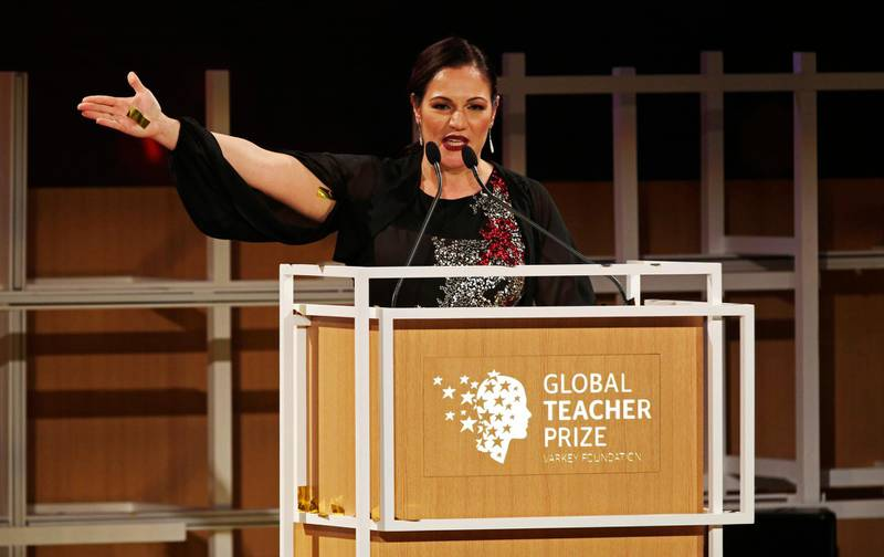 British school teacher Andria Zafirakou, with confetti still sticking to her skin, gestures toward other finalists at a ceremony awarding the Global Teacher Prize in Dubai, United Arab Emirates, Sunday, March 18, 2018. Zafirakou won the highly-competitive $1 million teaching prize on Sunday for her work with inner city children in London, helping students feel welcome and safe in a borough with one of the highest murder rates in the country and where English is frequently spoken as a second language at home. (AP Photo/Jon Gambrell)