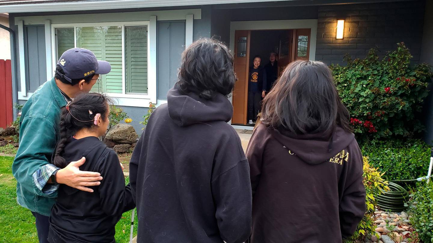 """This March 2020 photo provided by Graciela Tiscareño-Sato of Castro Valley, Calif., shows her with her husband and children, foreground, singing to her mother-in-law for her 79th birthday at a safe distance due to the COVID-19 coronavirus outbreak. """"Imagine now trying to explain to your child why she can't hug her grandmother,"""" she says. """"You're very much missing the human contact when you're standing 30 feet away."""" (Courtesy Graciela Tiscareño-Sato via AP)"""
